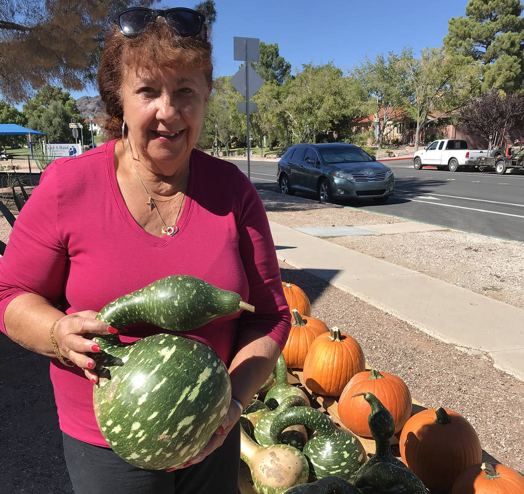 Hali Bernstein Saylor/Boulder City Review Tati Johnisee, a member of Boulder City United Methodist Church, shows off one of the swan gourds available at the church's pumpkin patch at the corner of ...