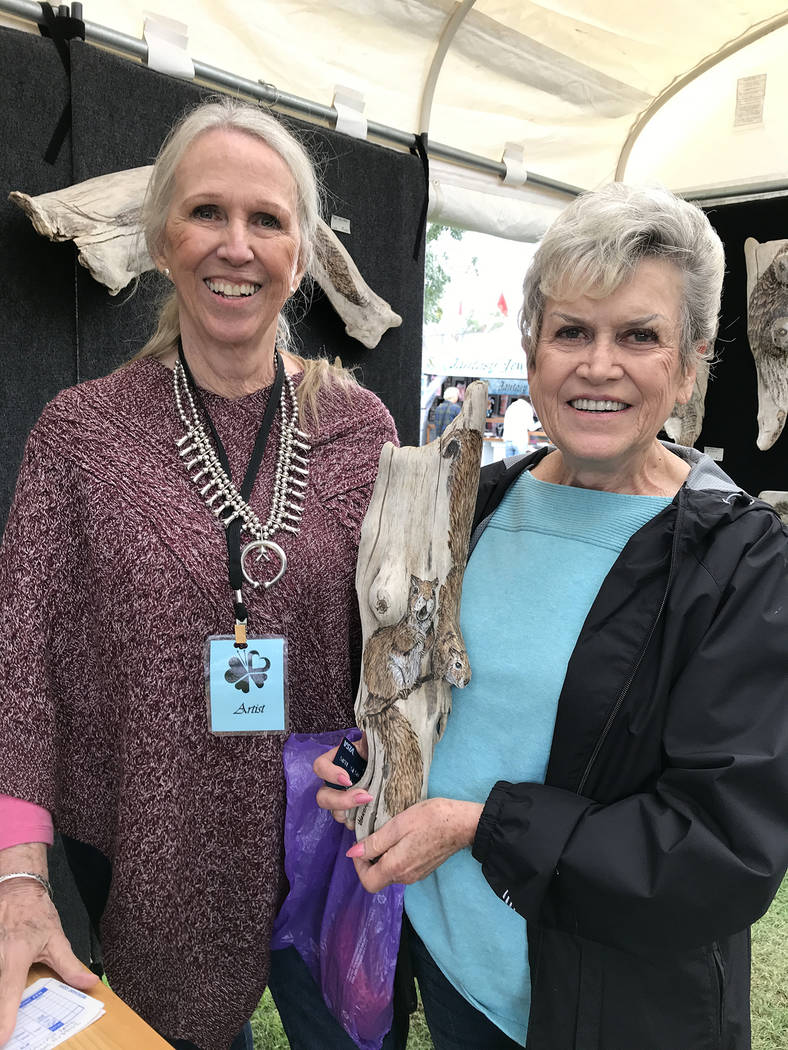 Hali Bernstein Saylor/Boulder City Review Boulder City artist Lynne Jordan, left, sells a pyrographic sculpture of squirrels on a piece of driftwood to Doni Stewart of Las Vegas on Sunday, Oct. 7, ...