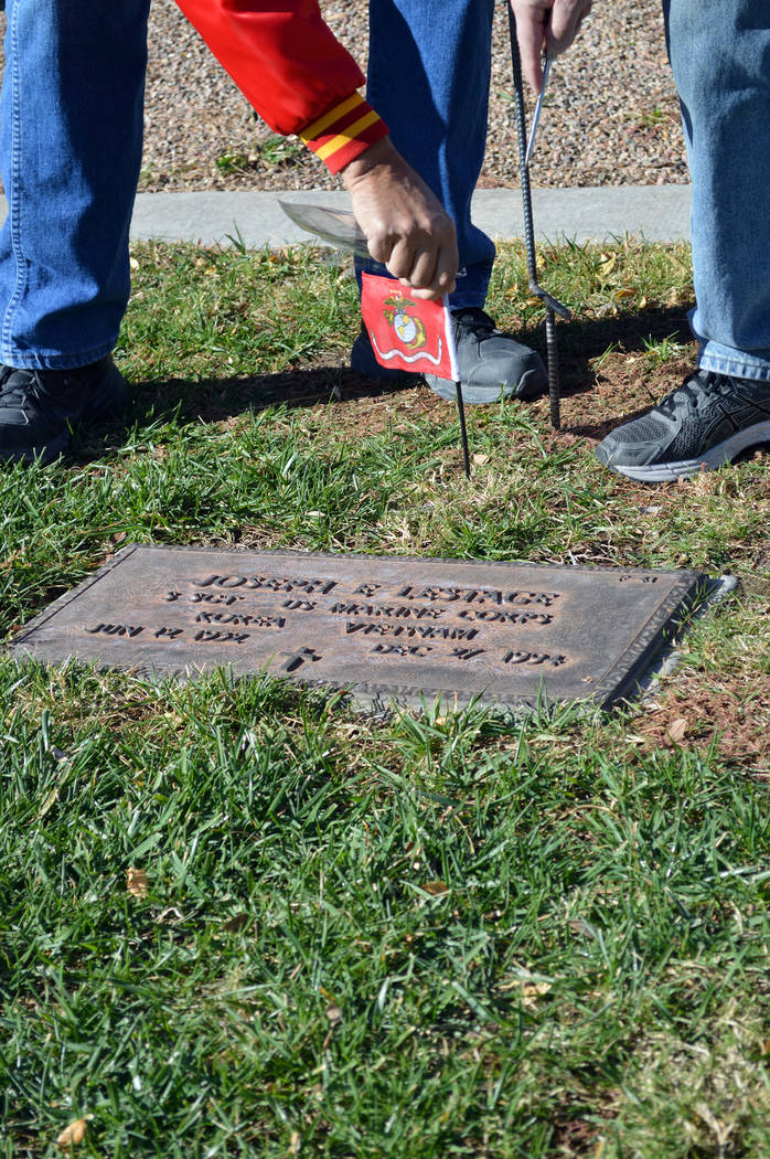 Celia Shortt Goodyear/Boulder City Review Don Ostertag places a United States Marine Corps flag on the grave of veteran at the Southern Nevada Veterans Memorial Cemetery in Boulder City on Friday, ...