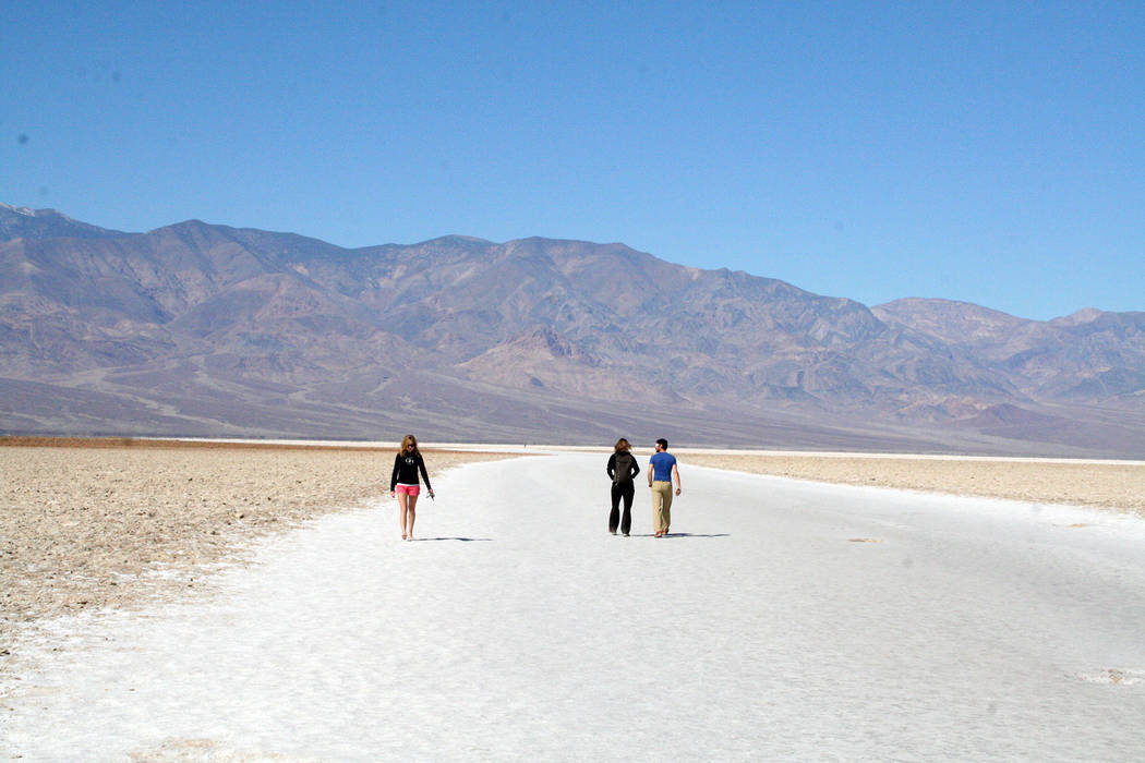 (Deborah Wall) Visitors to Badwater Basin in Death Valley National Park walk the salt flats.