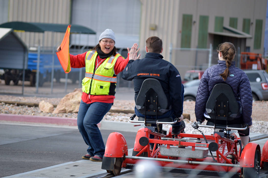 Mary Jo Lu of Rail Explorers high fives a couple on a pedal car during one of their rides. Rides will be available again, starting Saturday, Jan. 5.