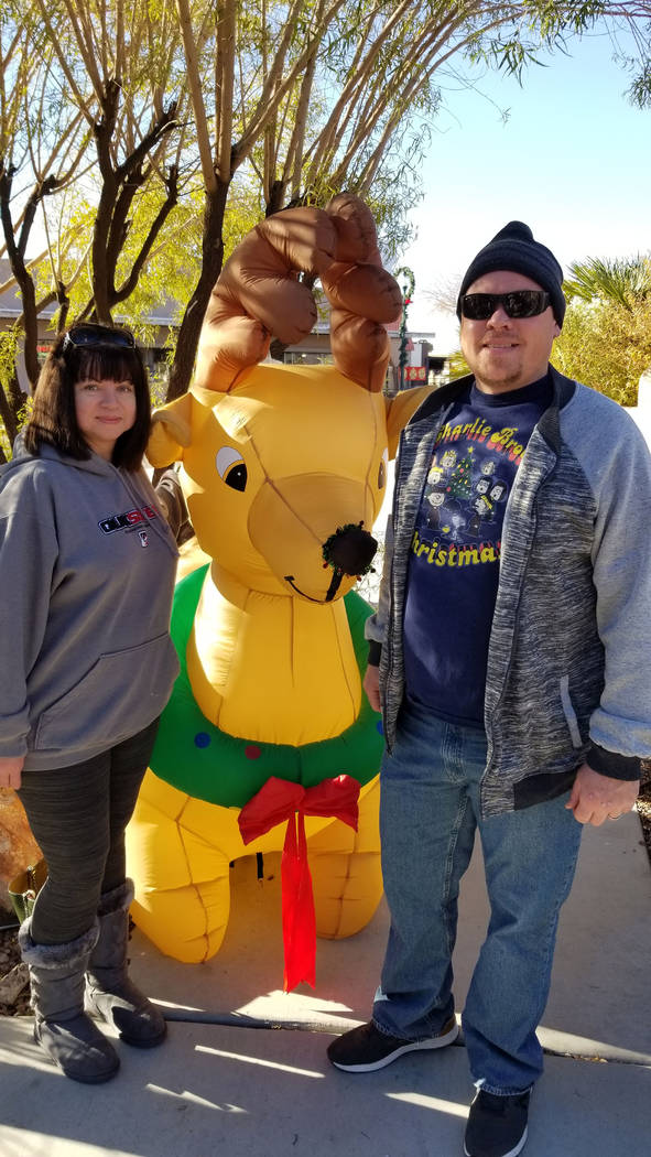 (Celia Shortt Goodyear/Boulder City Review) Michelle and Marcus Hillan take time for a photo with a Christmas reindeer at Breakfast with Santa on Saturday, Dec. 1.