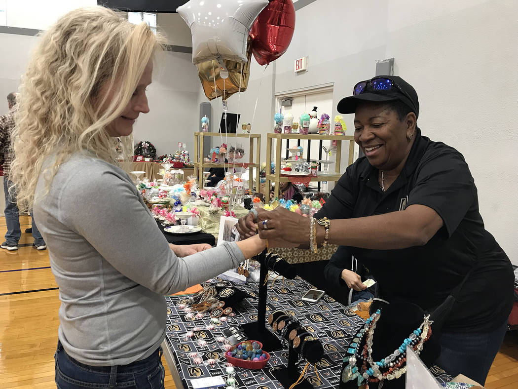 (Hali Bernstein Saylor/Boulder City Review) Terry Petty of Boulder City, left, gets some assistance from Ronnie Tice of Charmed as she tried on a bracelet during the 44th annual Doodlebug Craft Ba ...