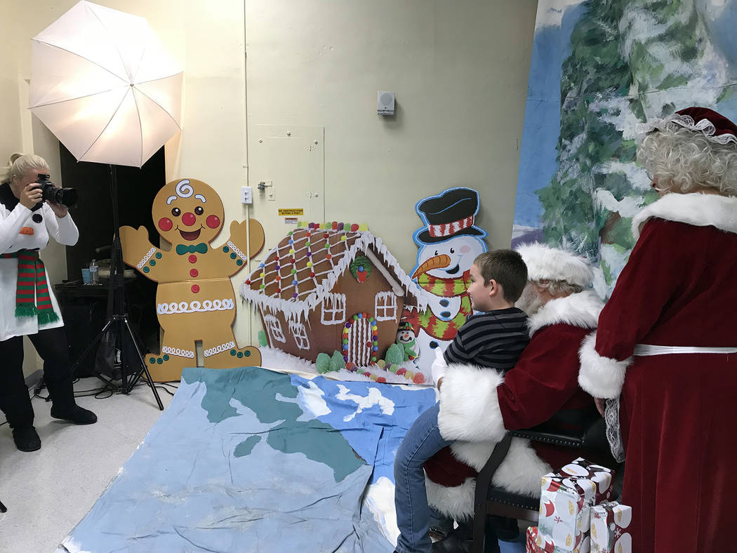 (Hali Bernstein Saylor/Boulder City Review) Pamela Leon of 28 Sunflowers, left, takes a picture of Kiptyn Simposn of Boulder City, 7, as he visits with Santa and Mrs. Claus on Saturday, Dec. 1, du ...