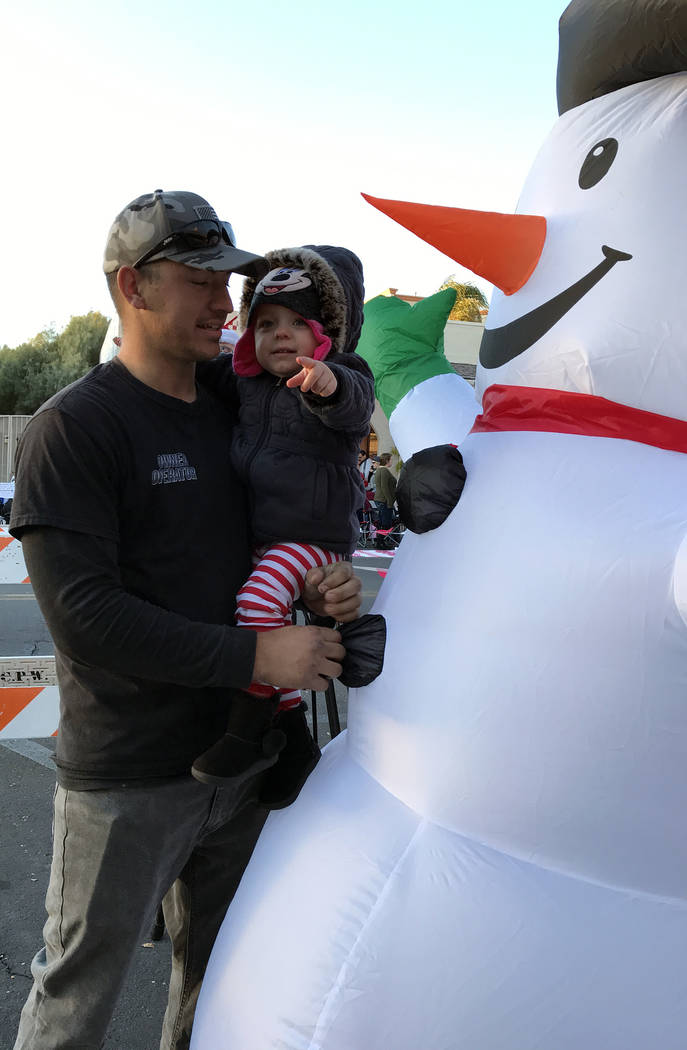 (Hali Bernstein Saylor/Boulder City Review) J.D. Owens entertains his 2-year-old daughter Braelynn Owens visiting an inflatable snowman before the start of Santa's Electric Night Parade on Saturda ...