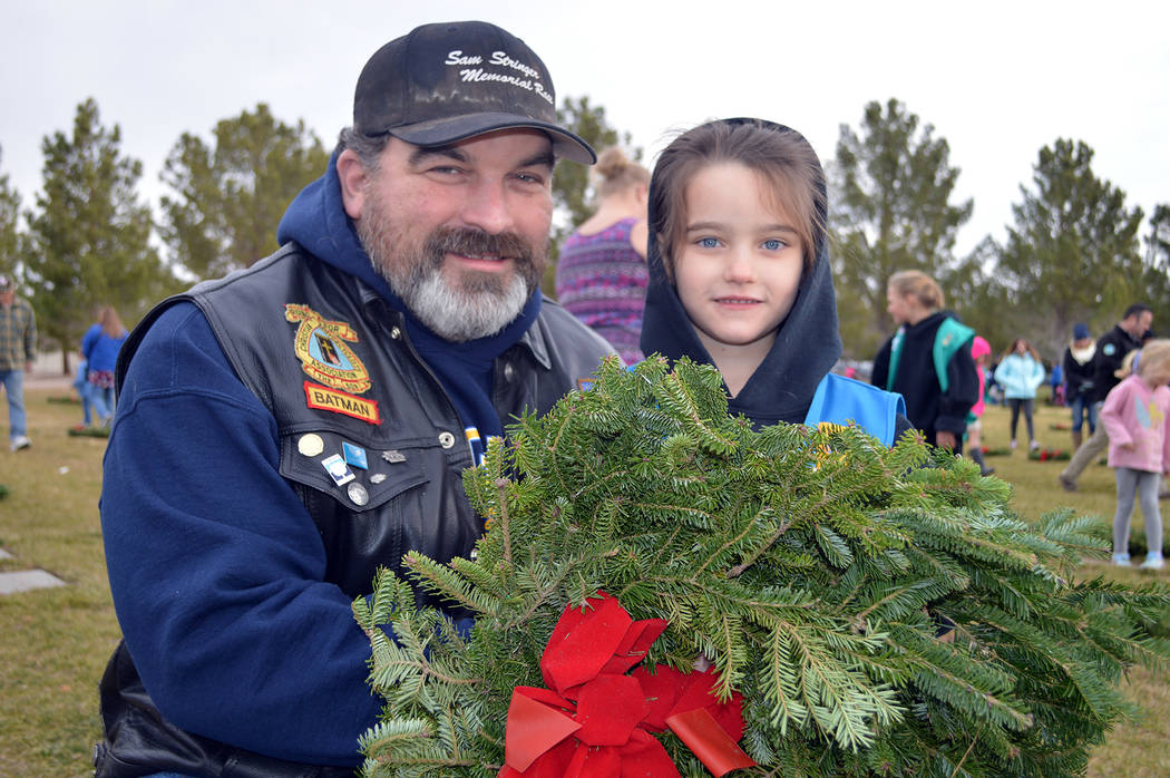 Mike Keeton and his daughter, Kenzie, lay a wreath on a veteran's grave at the Southern Nevada Veterans Memorial Cemetery during the 2017 observance of Wreaths Across America. This year's event wi ...