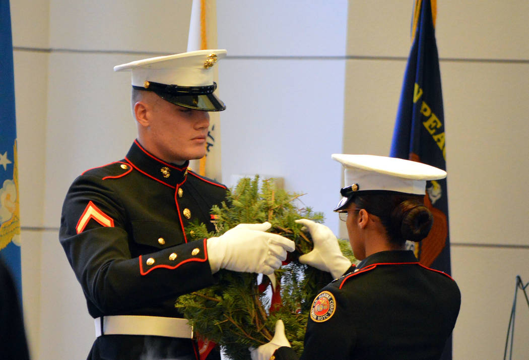 (Celia Shortt Goodyear/Boulder City Review) A United States Marine Corps Pfc. passes a wreath to a USMC Junior ROTC member during the placement of ceremonial wreaths, symbolizing pass the torch to ...