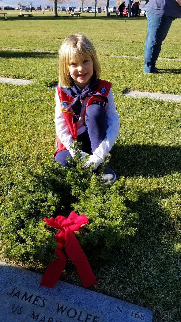 (Celia Shortt Goodyear/Boulder City Review) Seven-year-old Natalie Alexander places a wreath on a veteran's grave at the Southern Nevada Veterans Memorial Cemetery during Wreaths Across America on ...