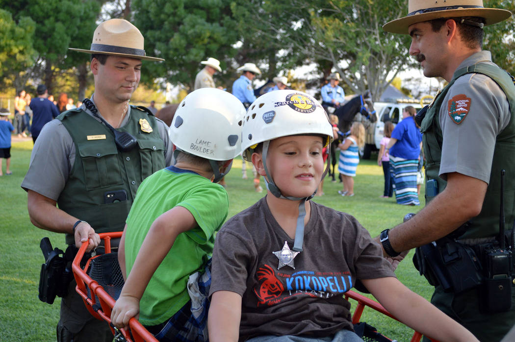 From August: Eight-year-old Adras Tambakis, center, and his brother Michael, 7, rode on stretcher from Canyon District Ranger Chris Cassling, right, and Mead District Ranger Ryan McCrea at Boulder ...