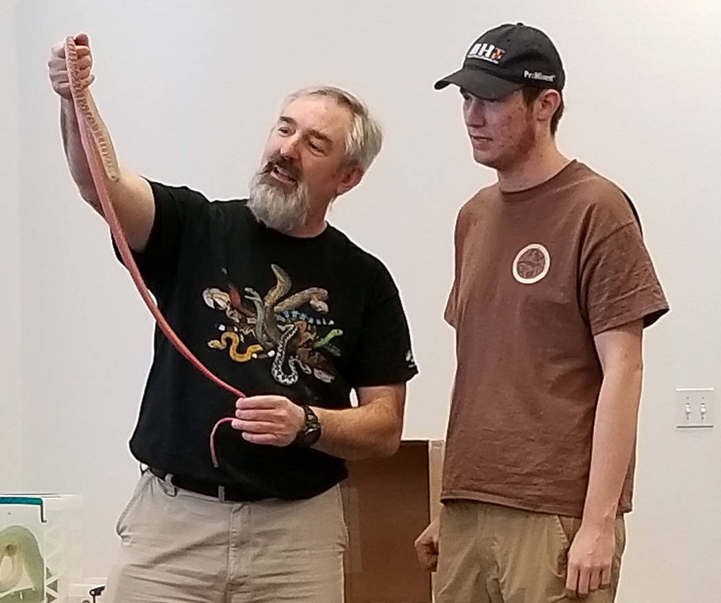 (Celia Shortt Goodyear/Boulder City Review) Chuck Meyer, left, shows his red racer snake with his son, Charlie, at the Boulder City Library on Jan. 3. The animal event was part of the winter readi ...