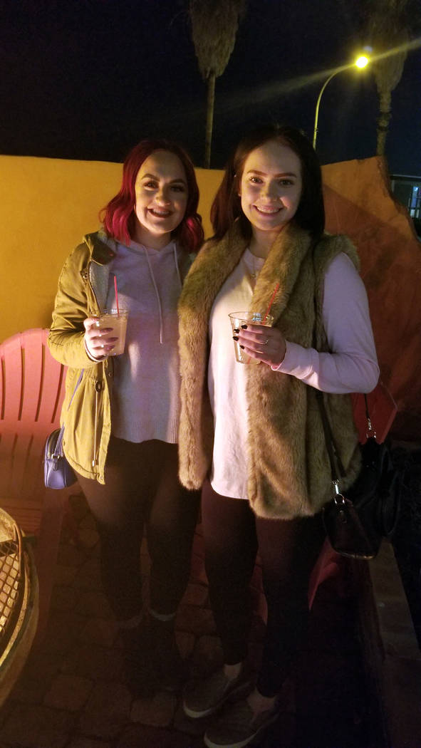 (Celia Shortt Goodyear/Boulder City Review) Tori Humphries, left, and Ashlynn Marlo hang out at the fire during the third annual Xi Zeta Rosie Roll pub crawl on Friday, Feb. 22.