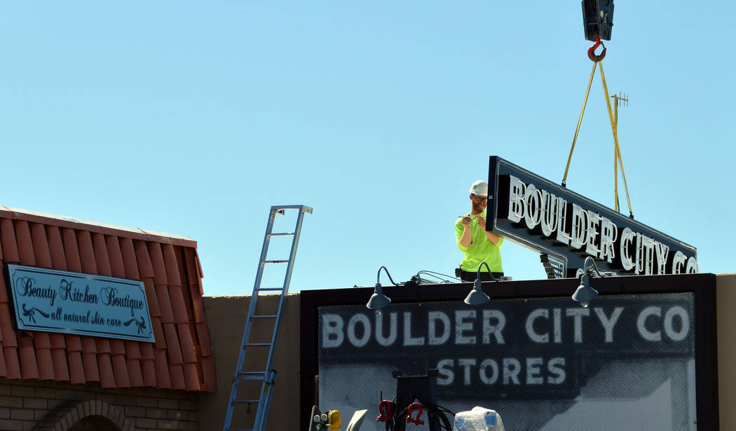 (Celia Shortt Goodyear/Boulder City Review) A worker with High Impact Signs installs a new sign ...