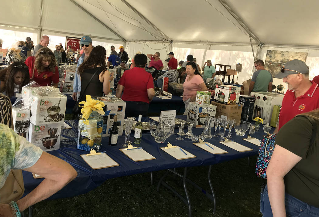 (Hali Bernstein Saylor/Boulder City Review) People place bids on a variety of items during the ...