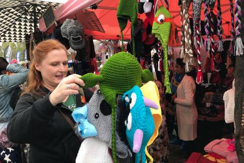 Adar Bagus of Las Vegas looks at handmade hats during Art in the Park in 2018. This year's fest ...
