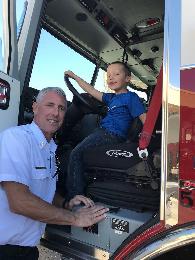 (Hali Bernstein Saylor/Boulder City Review) Interim Fire Chief Steve Walton shows his grandson ...