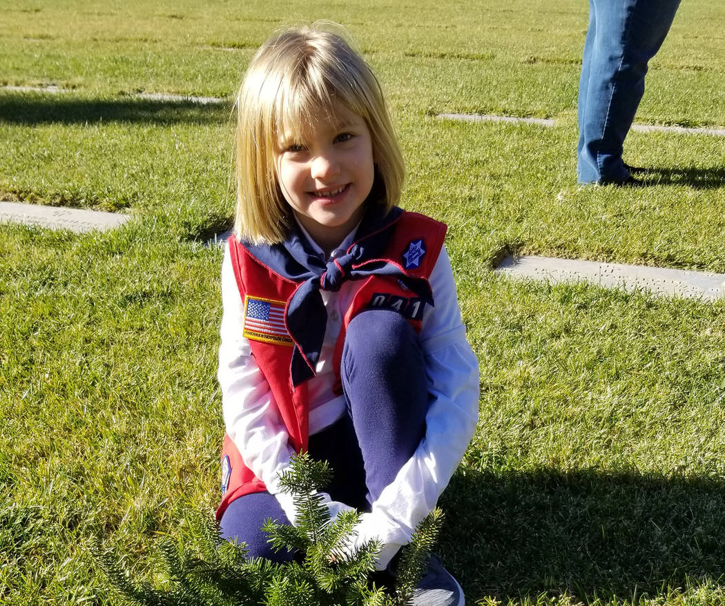 Seven-year-old Natalie Alexander placed a wreath on a veteran's grave during the 2018 Wreaths ...