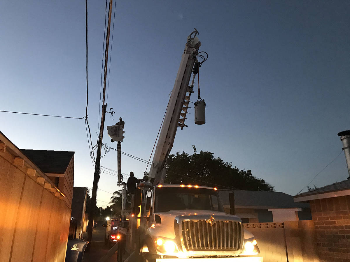 """(Norma Vally) A crew from the utility department repairs a transformer """"can"""" that ..."""