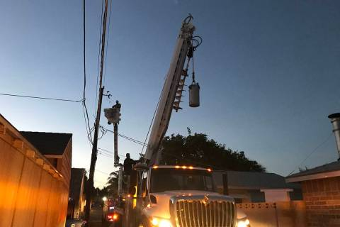 "(Norma Vally) A crew from the utility department repairs a transformer ""can"" that ..."