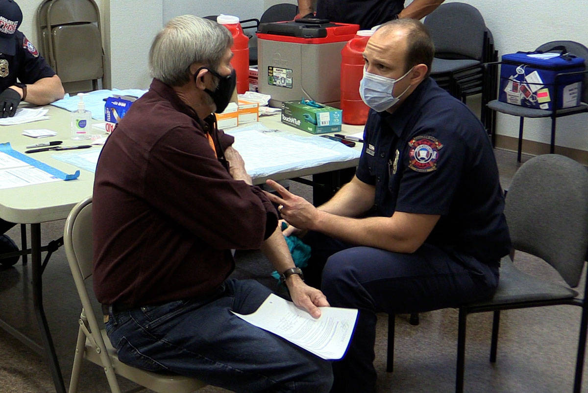 Boulder City Boulder City Firefighter Nick Giles prepares to give resident Fred Bachhuber the ...