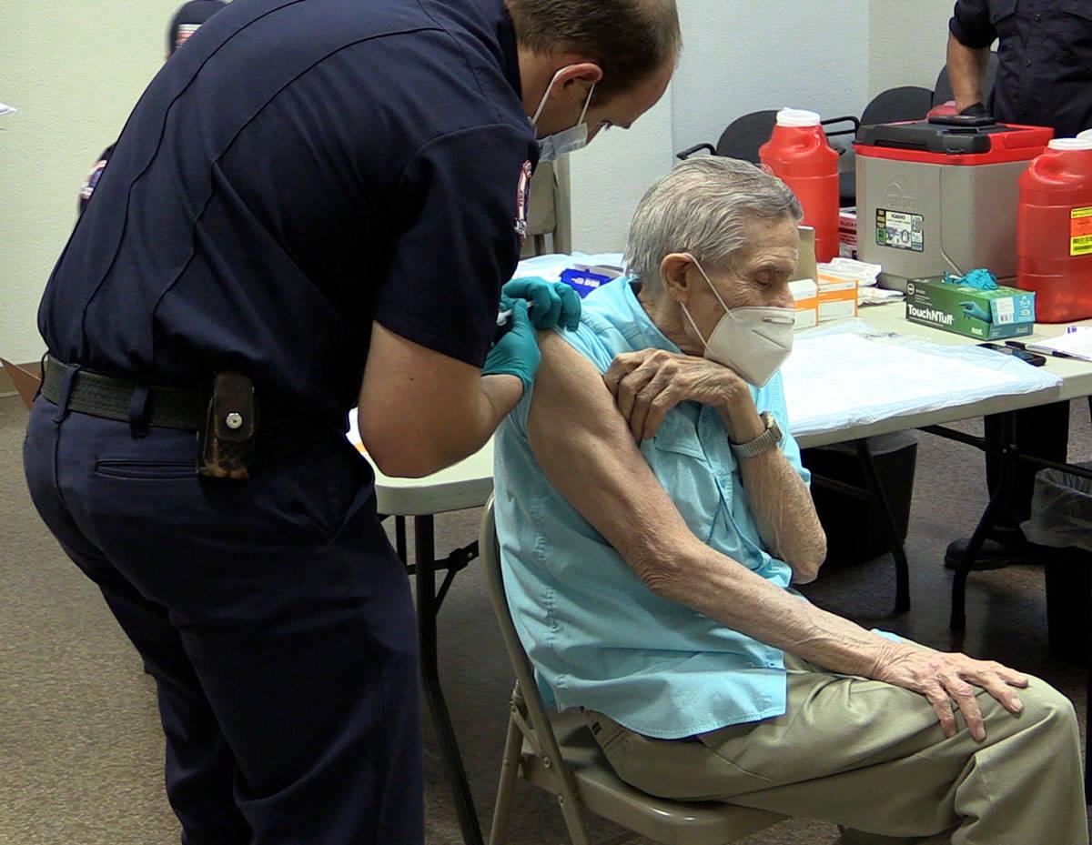 Boulder City Boulder City Firefighter Nick Giles gives resident Joe Lambert the COVID-19 vaccin ...