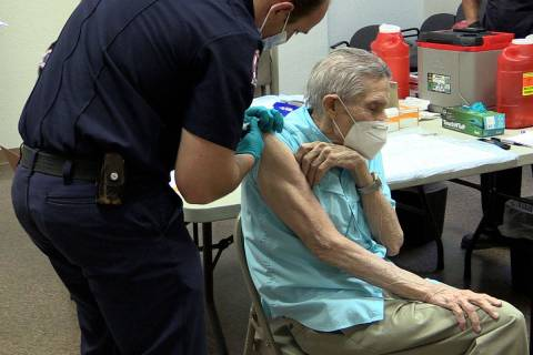 Boulder City Boulder City Firefighter Nick Giles gives resident Joe Lambert the COVID-19 vaccin ...
