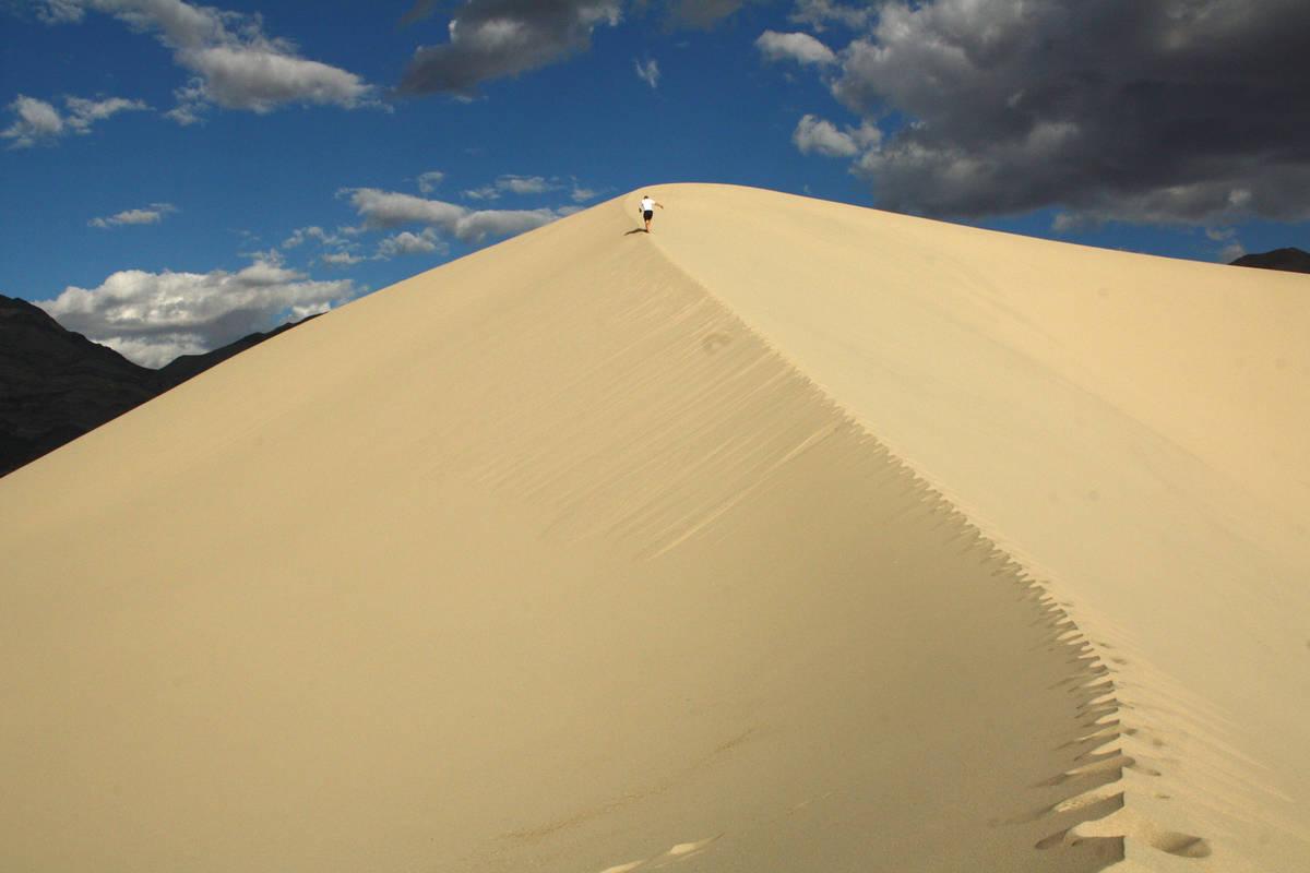 (Deborah Wall) A hiker makes his way up the soft sand at Eureka Dunes at Death Valley National ...