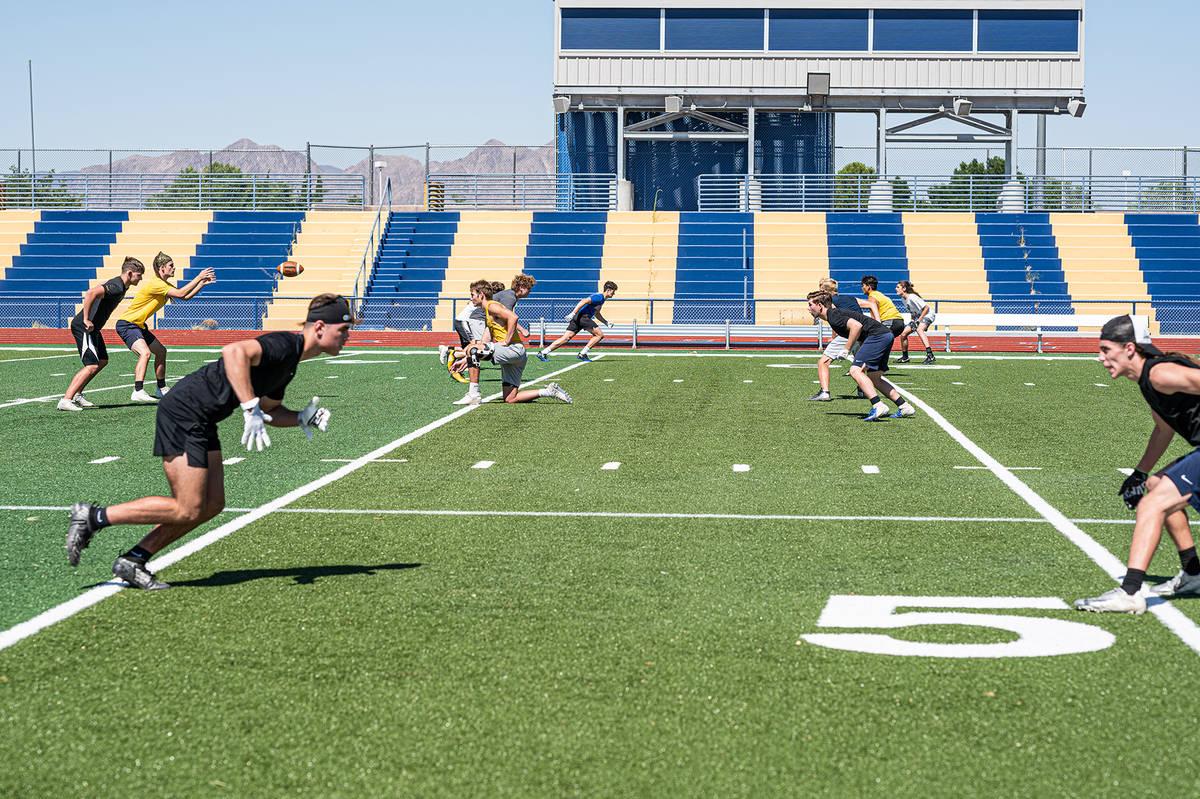 Members of Boulder City High School's varsity football team, seen running drills in July, are ...
