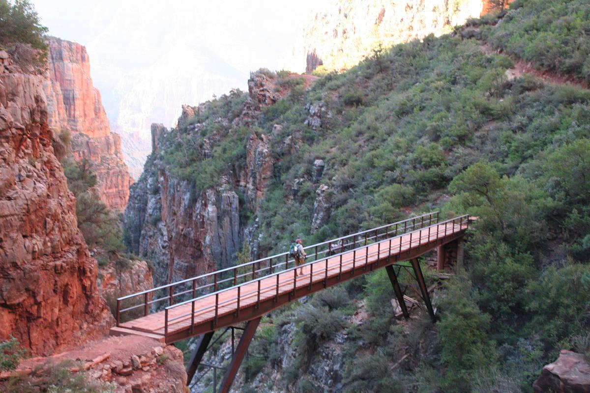 (Deborah Wall) A hiker walks across the Redwall Bridge along the North Kaibab Trail at the Gran ...