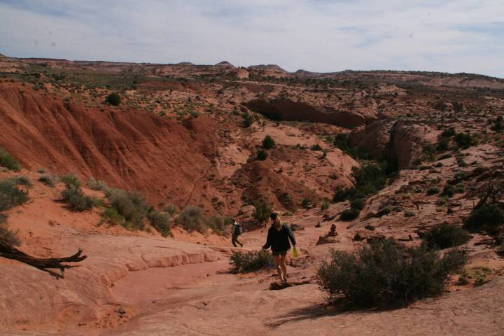 (Deborah Wall) From the trailhead hikers head down the slickrock using cairns to guide the way ...