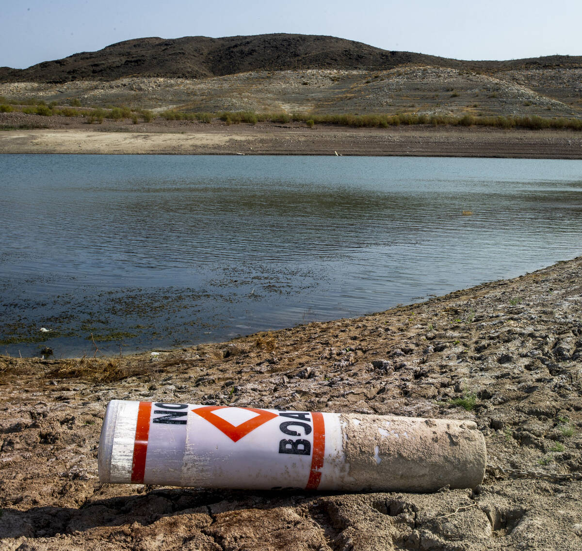 (L.E. Baskow/Special to the Boulder City Review) A buoy sits on the shore from low water near B ...